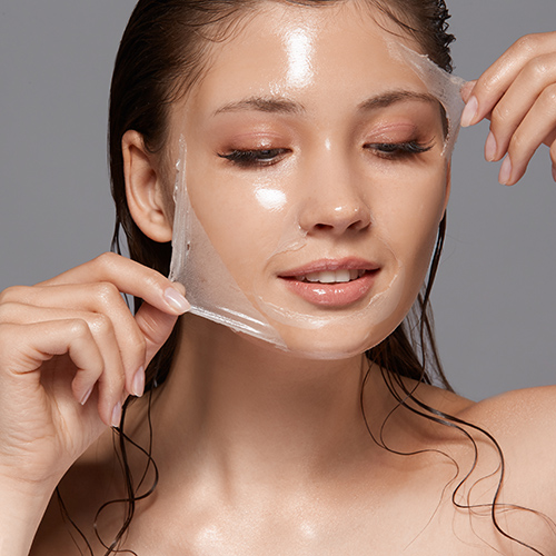 female with wet hair and naked shoulders removing trasparent peeling mask and looking down